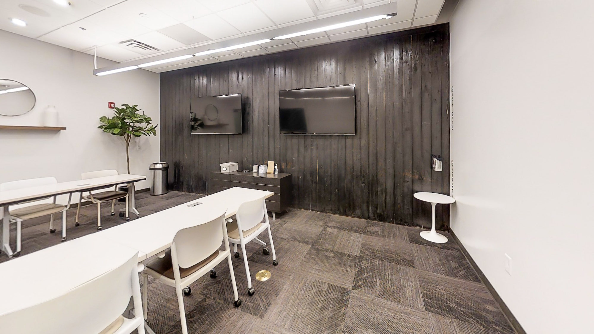 Two mounted LED screens and wood accent wall in creative Atlanta meeting room