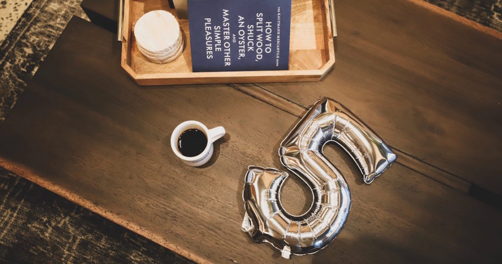 Coffee mug and silver foil balloon on coffee table