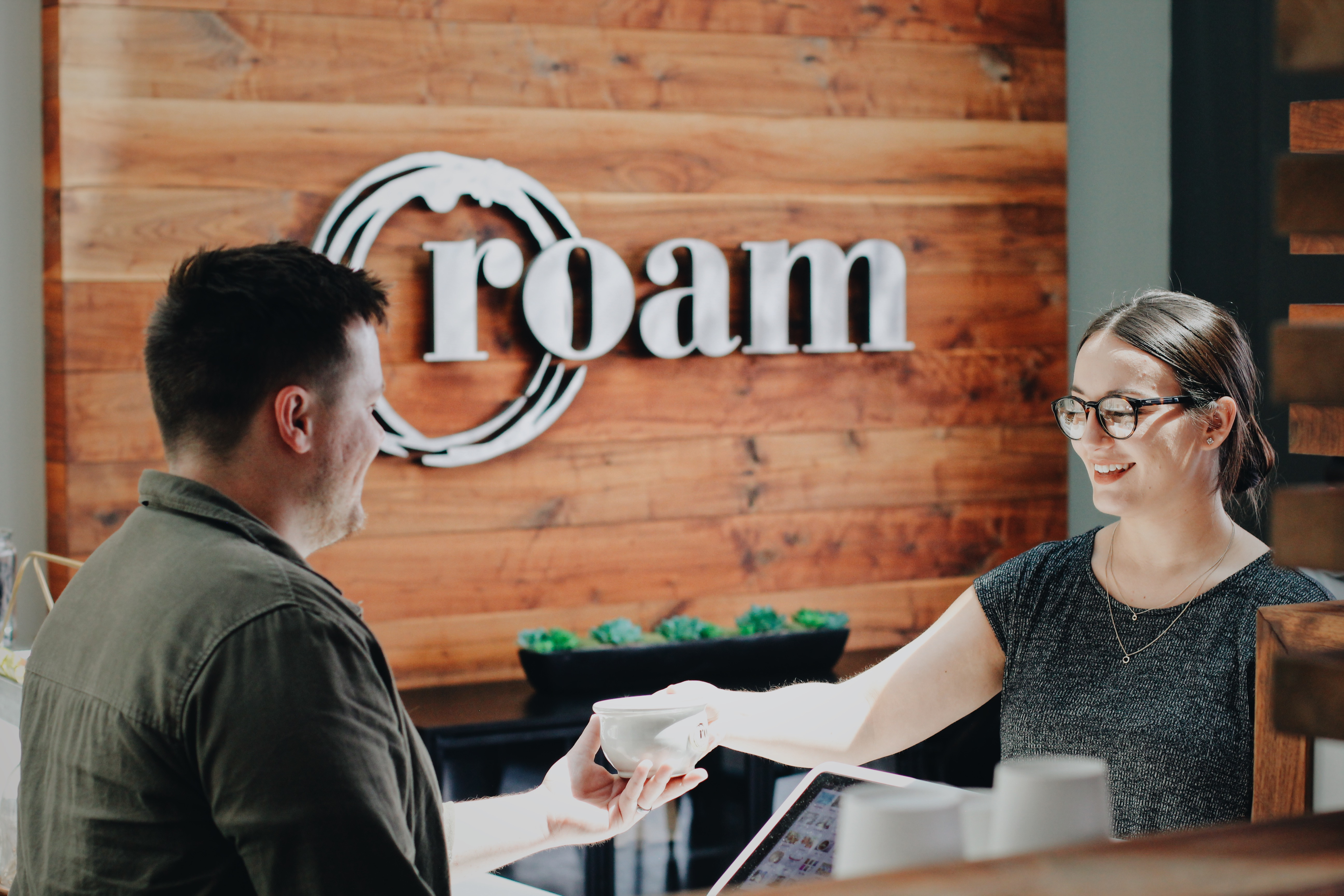 Employee serving coffee at Roam